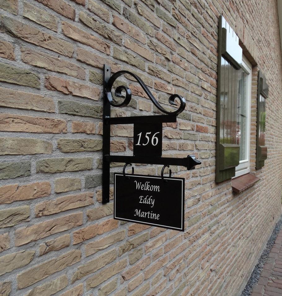uithangbord handgeschilderd met huisnummer en krul